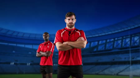 rugby shirt : Animation of a Caucasian and African American male rugby players with arms crossed and looking to camera with stadium in the background Stock Footage