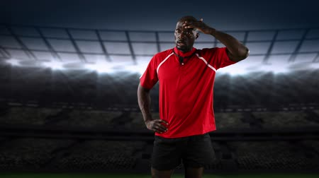 quadris : Animation of a African American male rugby player standing with hands on his hips and looking to camera with floodlit stadium in the background Stock Footage
