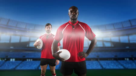 rúgbi : Animation of an African American and a Caucasian male rugby player holding rugby balls and looking to camera with floodlit stadium in the background