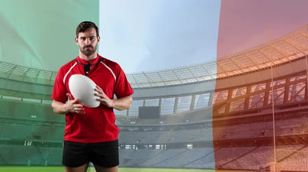 rugby shirt : Animation of a Caucasian male rugby player playing with a ball and looking to camera with blowing Italian flag and stadium in the background Stock Footage