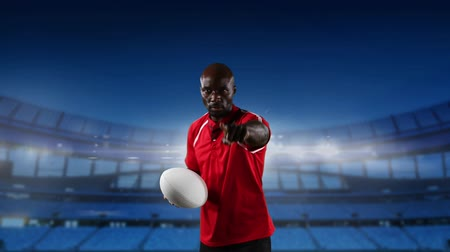 rugby ball : Animation of an African American male rugby player pointing, playing with a ball and looking to camera with floodlit stadium in the background Stock Footage