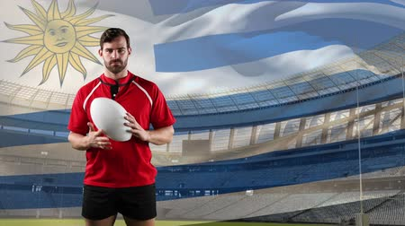 Уругвай : Animation of a Caucasian male rugby player playing with a ball and looking to camera with blowing flag of Uruguay and stadium in the background Стоковые видеозаписи