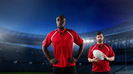 rugby shirt : Animation of an African American male rugby player with hands on hips and a Caucasian male rugby player holding a ball and looking to camera with floodlit stadium in the background Stock Footage