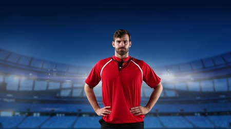 rugby shirt : Animation of a Caucasian male rugby player standing with hands on his hips and looking to camera with floodlit stadium in the background Stock Footage