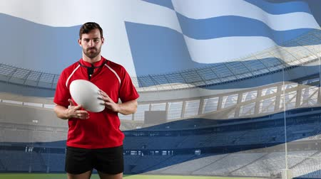 rúgbi : Animation of a Caucasian male rugby player holding a ball and looking to camera with blowing Greek flag and stadium in the background