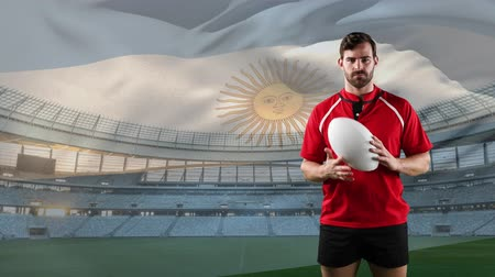 rugby shirt : Animation of a Caucasian male rugby player holding and throwing a ball and looking to camera with blowing Argentinian flag and stadium in the background Stock Footage
