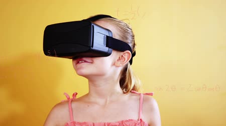 formulae : Animation of a Caucasian schoolgirl wearing a VR headset and using her hands to move virtual mathematical formulae Stock Footage