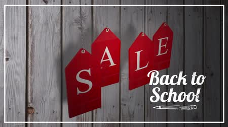 expectativa : Animation of the words Back To School Sale in white and on red hanging tags on a wooden background