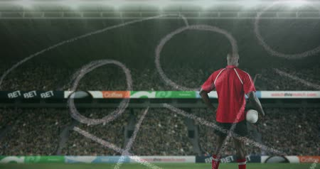 сосредоточиться на переднем плане : Animation of a back view of an African American male rugby player standing, holding a ball in his hand and looking around with hand drawn game plan in the foreground and sports stadium in the background 4k