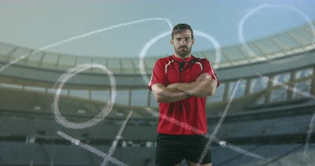rugby shirt : Animation of a Caucasian male rugby player standing with crossed arms and looking to camera with hand drawn game plan in the foreground and sports stadium in the background 4k Stock Footage