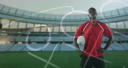 rúgbi : Animation of an African American male rugby player standing, holding a ball under his arm and looking to camera with hand drawn game plan in the foreground and sports stadium in the background 4k