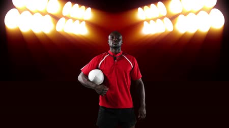 rugby shirt : Animation of an African American male rugby player holding a ball and looking to camera with flickering orange stadium spotlights in the background