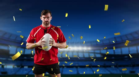 rugby shirt : Animation of a Caucasian male rugby player playing with a ball and looking to camera with golden confetti falling and a floodlit sports stadium in the background