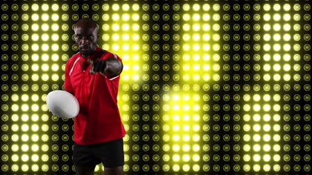 rúgbi : Animation of an African American male rugby player playing with a ball and looking to camera with digital display of moving yellow lights in the background