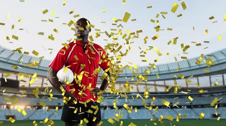 rugby ball : Animation of an African American male rugby player holding a ball and looking around with golden confetti falling and sports stadium in the background Stock Footage