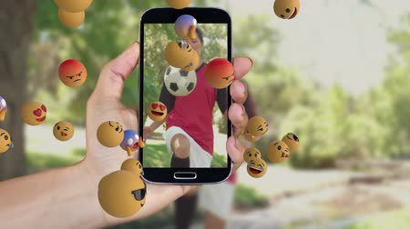 lol : Animation of emoji icons with a person taking photos of female football players on a smartphone in the background Stock Footage