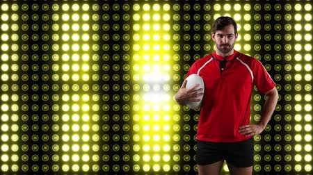 rugby shirt : Animation of a Caucasian male rugby player holding a ball and looking to camera with digital display of moving yellow lights in the background Stock Footage