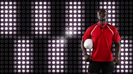 rugby shirt : Animation of a African American male rugby player holding a ball and looking to camera with digital display of moving white lights in the background