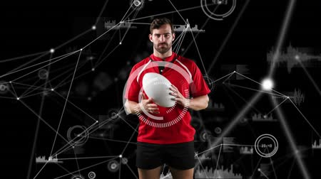 rugby shirt : Animation of a Caucasian male rugby player playing with a ball and looking to camera with connection links and circles spinning and data appearing on a black background Stock Footage