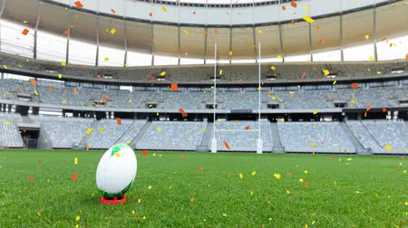 rúgbi : Animation of a rugby ball at sports stadium with red and yellow confetti falling Vídeos