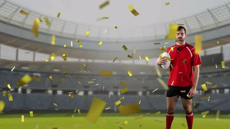 rugby ball : Animation of a Caucasian male rugby player holding a ball and looking to camera with golden confetti falling and a sports stadium in the background