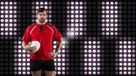 rugby shirt : Animation of a Caucasian male rugby player holding a ball and looking to camera with digital display of moving white lights in the background Stock Footage