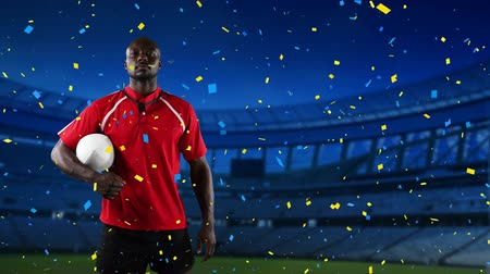 rugby shirt : Animation of an African American male rugby player holding a ball and looking to camera with blue and yellow confetti falling and sports stadium in the background