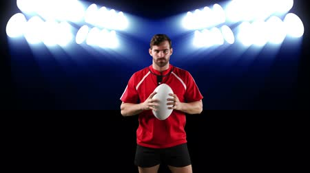 rugby shirt : Animation of a Caucasian male rugby player playing with a ball and looking to camera with flickering blue stadium spotlights in the background Stock Footage