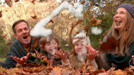 free throw : Animation of a happy Caucasian parents with a son and daughter lying in fallen leaves in autumn and throwing them in the air while a house icon appearing in the foreground