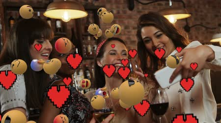 lol : Animation of emoji icons with a multi-ethnic group of female friends taking a selfie in the background Stock Footage