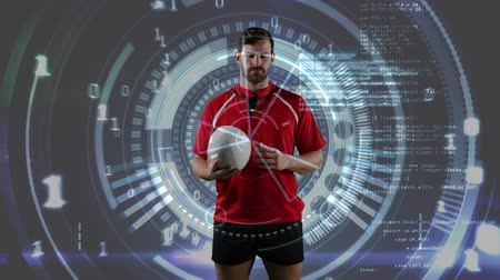 rugby shirt : Animation of a Caucasian male rugby player standing, playing with a ball and looking to camera with binary coding, circles spinning and medical data appearing on a grey background Stock Footage