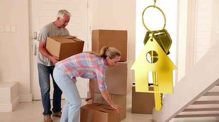 mülkiyet : Animation of golden house keys and house shaped key fob spinning over a Caucasian couple moving in and carrying boxes to their home in the background