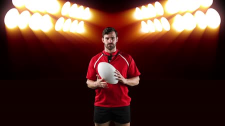 antecipação : Animation of a Caucasian male rugby player playing with a ball and looking to camera with flickering orange stadium spotlights in the background Vídeos