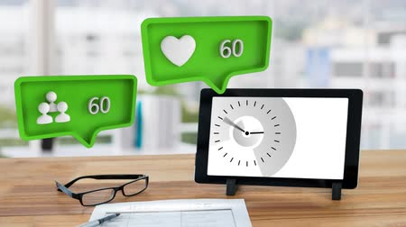 cem : Animation of green speech bubbles with a heart and a people symbol and increasing numbers from zero to one hundred with a clock displayed on a tablet computer and reading glasses on a table top in the background