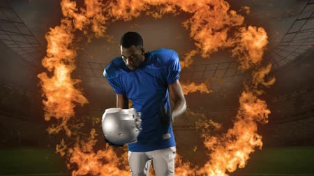 antecipação : Animation of a front view of a male African American American football player putting a helmet on while flames appearing in front of a floodlit sports stadium in the background