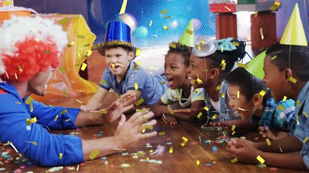 peruca : Animation of multi-ethnic children and a clown at a birthday party laughing and celebrating, while golden confetti is falling in the foreground