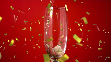 flet : Animation of a close up of champagne being poured into a glass with golden confetti falling on a red background