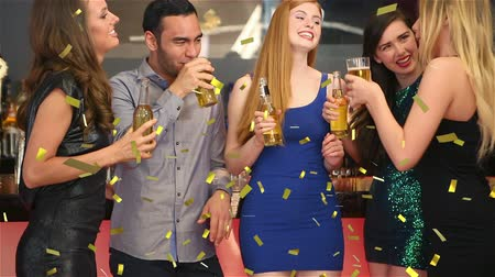 beer house : Animation of a group of young multi-ethnic male and female friends celebrating and drinking, while golden confetti is falling in the foreground