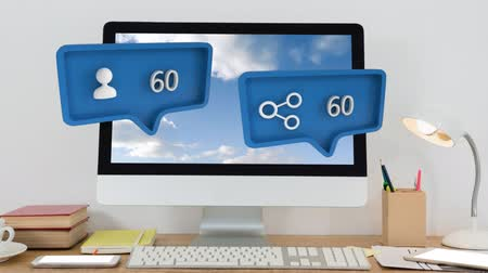 compleição : Animation of blue speech bubbles with a share and person symbol and increasing numbers from zero to one hundred, over a computer, lamp and books on a table in the background Stock Footage