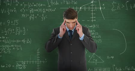 matemático : Animation of a young Caucasian man standing and massaging his temples trying to solve a problem in front of a green chalkboard with moving mathematical calculations written in chalk Stock Footage