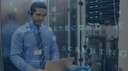 сосредоточиться на переднем плане : Animation of a Caucasian man working in a computer server room using headset and a laptop, with data security warning messages in the foreground Стоковые видеозаписи