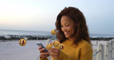 lol : Animation of emoji icons flying up with a young mixed race woman smiling and using a smartphone in the background 4k Stock Footage
