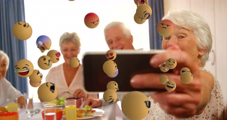lol : Animation of emoji icons flying from left to right with a group of senior Caucasian friends taking a selfie in the background 4k