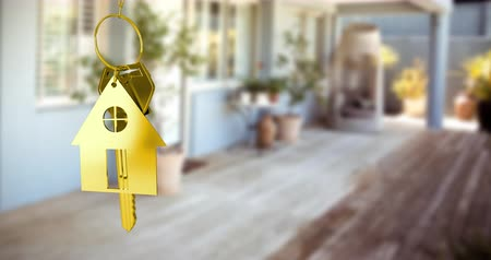 mülkiyet : Animation of golden house keys and house shaped key fob hanging over an out of focus terrace 4k