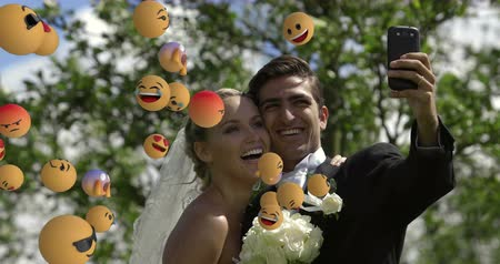 risonho : Animation of emoji icons flying from left to right with a young just married Caucasian couple taking a selfie at a wedding in the background 4k Vídeos