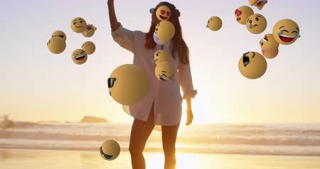 risonho : Animation of emoji icons flying right to left with a young Caucasian woman taking a selfie on a beach in the background 4k Vídeos
