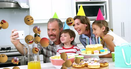 lol : Animation of emoji icons flying from left to right with a Caucasian man taking a selfie of his son, daughter and wife, wearing party hats at a birthday party in the background 4k