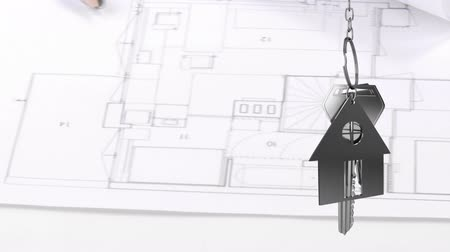 фасонный : Animation of silver house keys and house shaped key fob hanging over architectural drawing, a ruler and a compass in the background