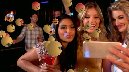 lol : Animation of emoji icons flying from left to right with young Caucasian female friends taking a selfie in the background