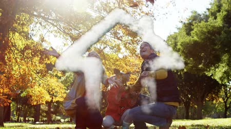 mülkiyet : Animation of a house shape made of cloud floating with a Caucasian family throwing leaves in a park in autumn in the background Stok Video